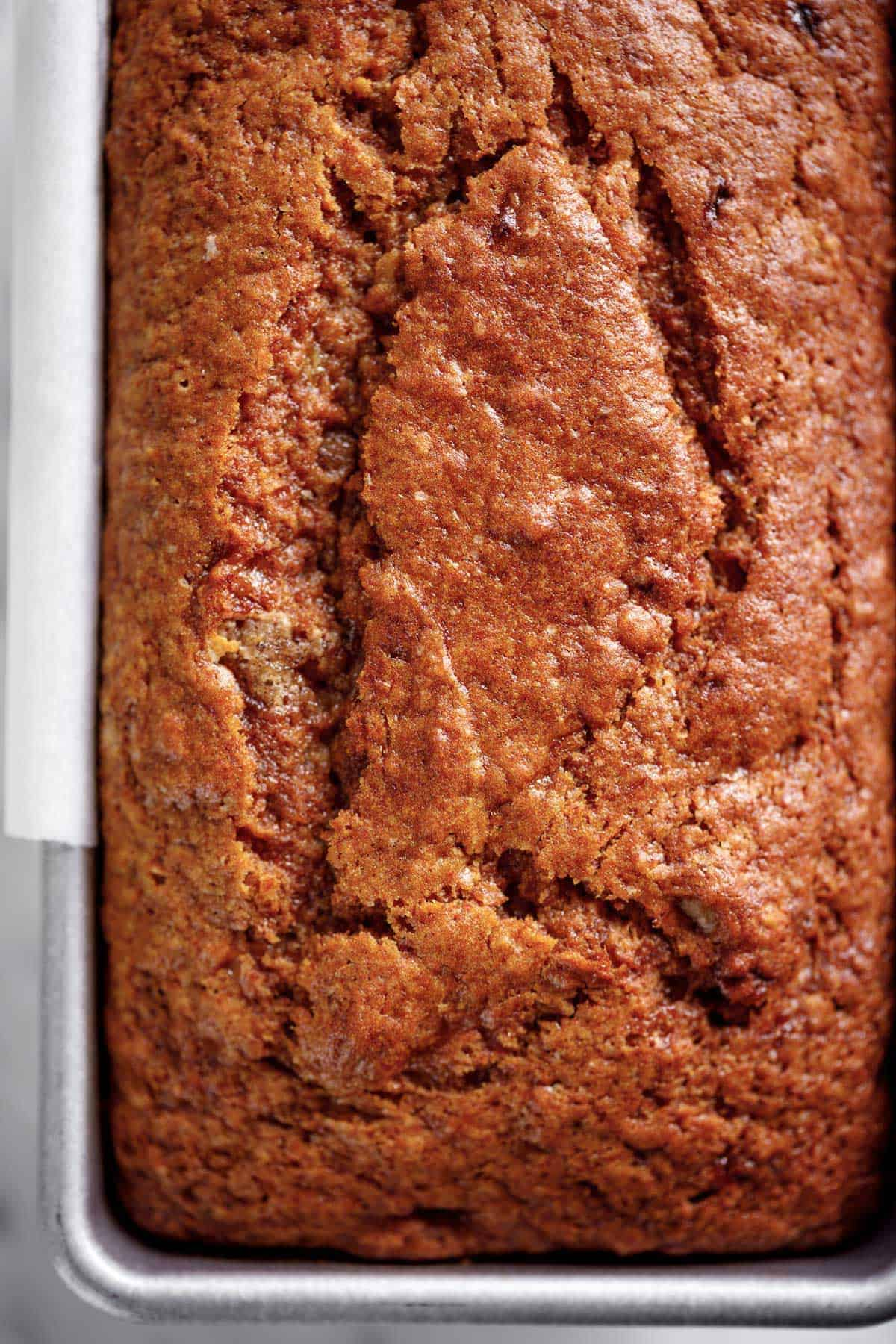 A loaf of moist banana bread baked in a loaf tin | craveitall.com