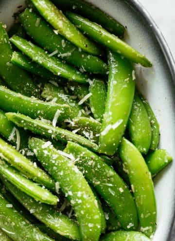 Cacio E Pepe Sugar Snap Peas served in a white bowl with a black rim. Garnished with extra parmesan cheese and cracked black pepper. | craveitall.com