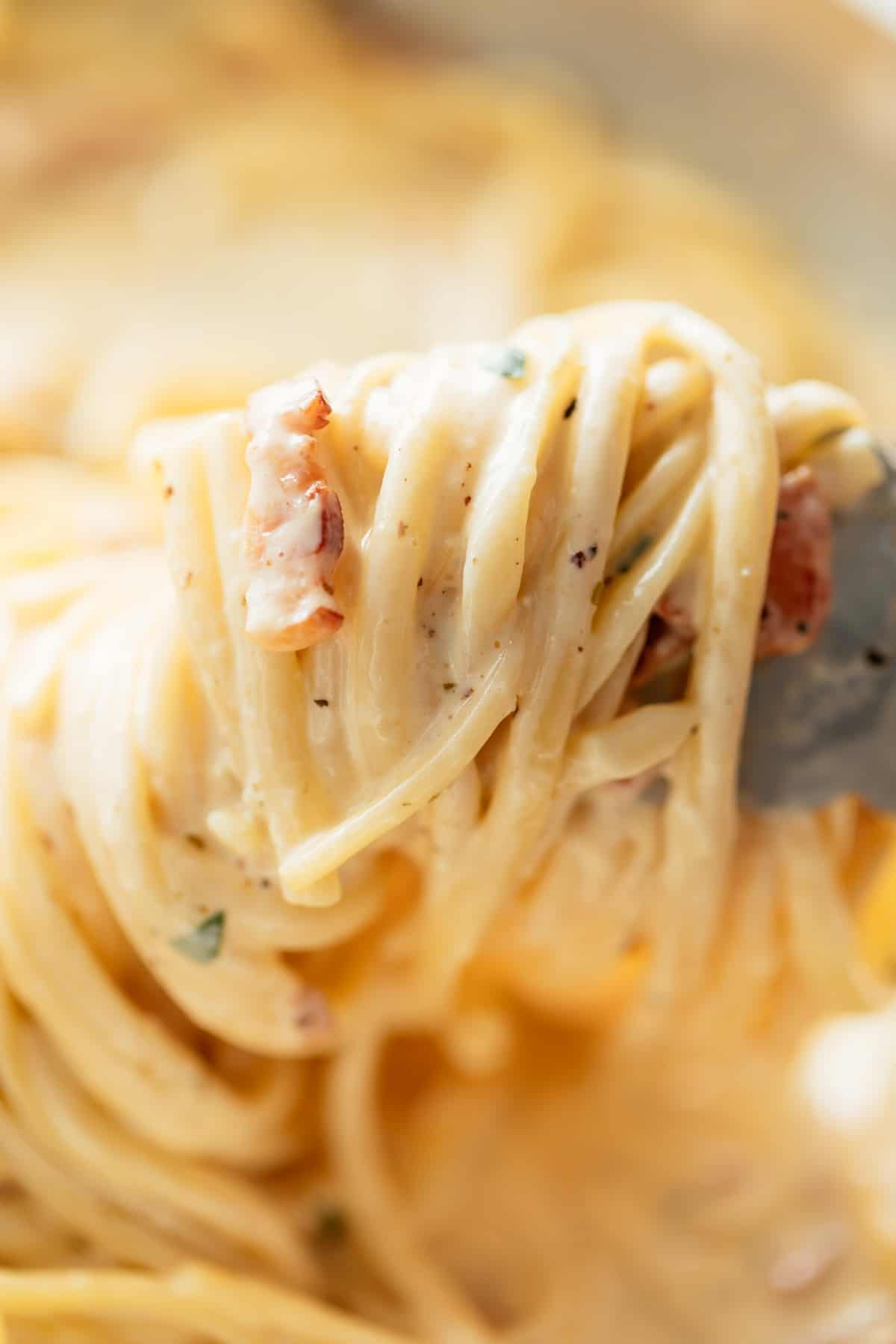 Tongs swirl and pick up Fettuccine Alfredo in a silver pan | craveitall.com