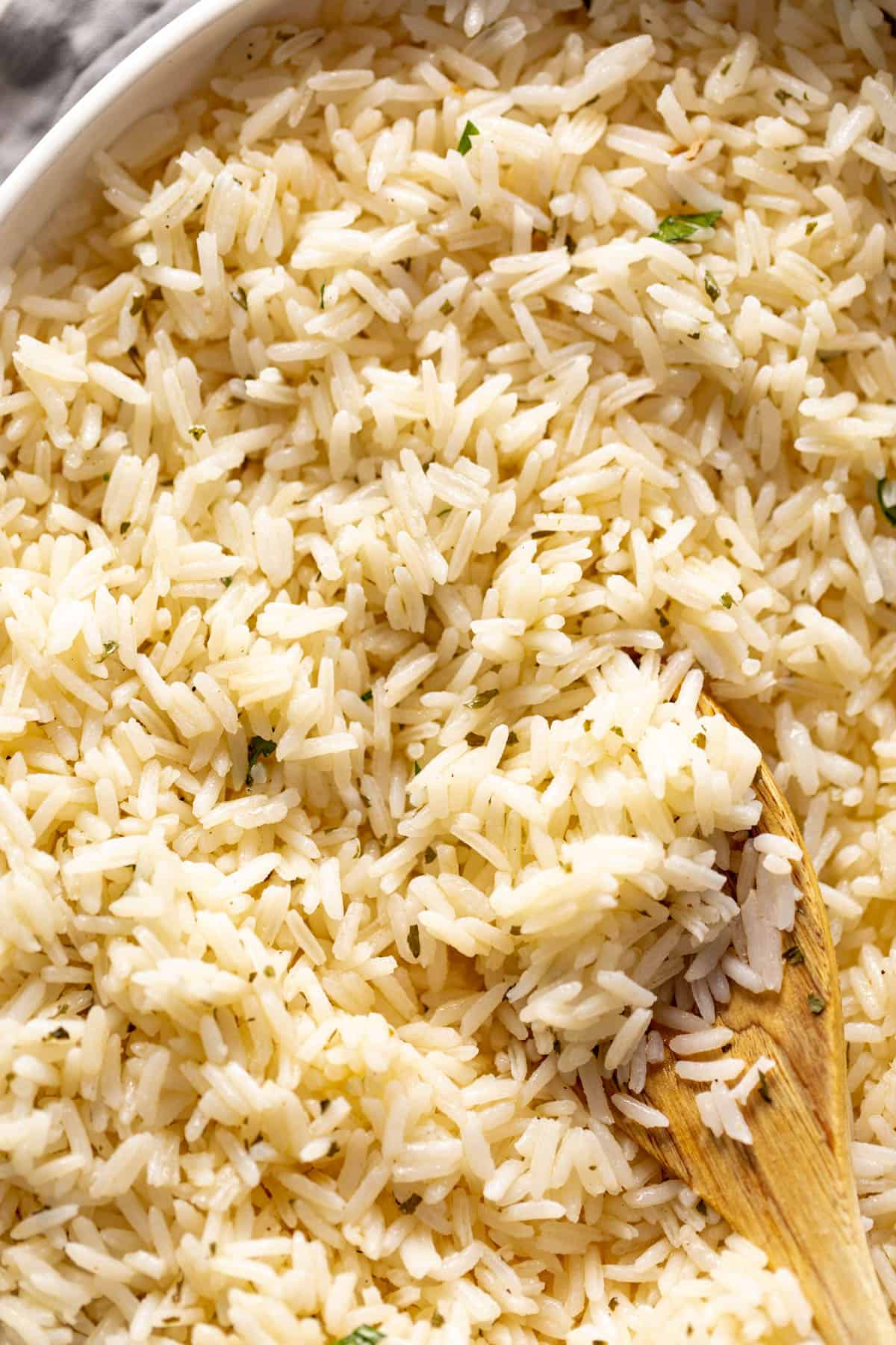 Garlic Butter Rice served with a wooden spoon. | craveitall.com