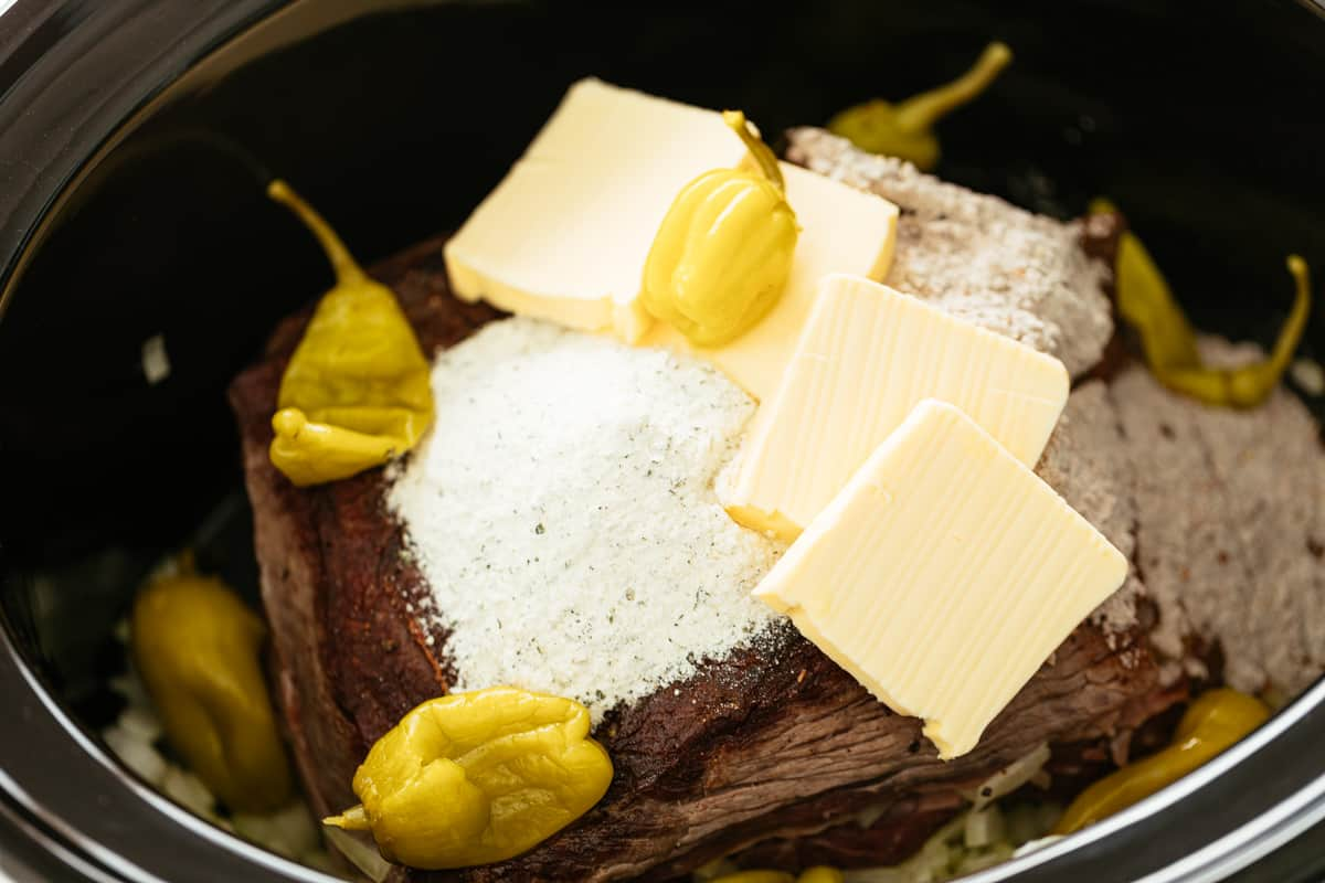 Combined ingredients for a Mississippi Pot Roast in a black slow cooker bowl   craveitall.com