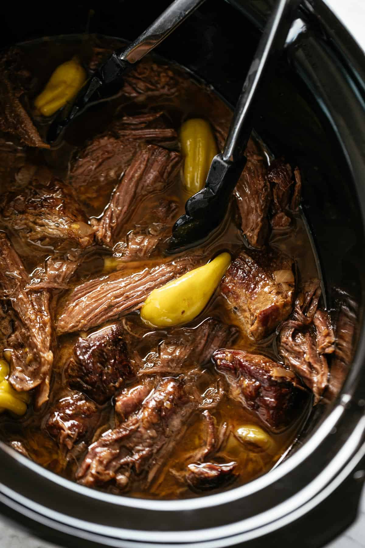 Mississippi Pot Roast cooked low and slow in a black slow cooker bowl.   craveitall.com