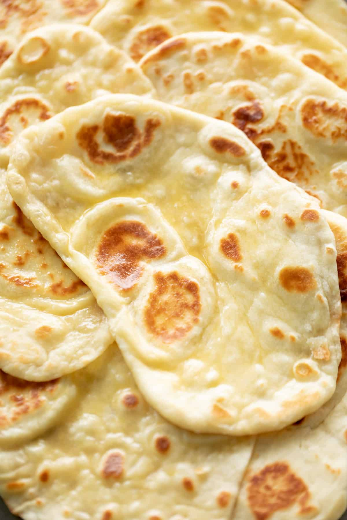 Soft Naan bread with melted butter and crushed garlic | craveitall.com