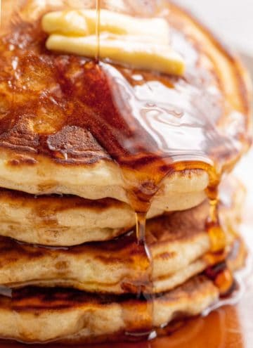 A stack of Fluffy Pancakes on a white plate served with butter and drizzled with maple syrup.   craveitall.com