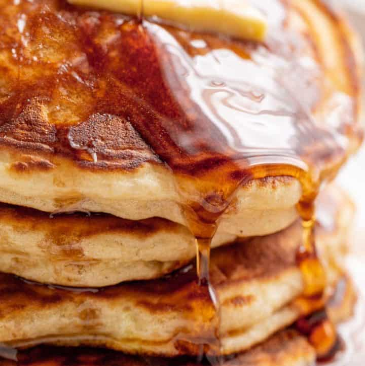 A stack of Fluffy Pancakes on a white plate served with butter and drizzled with maple syrup. | craveitall.com